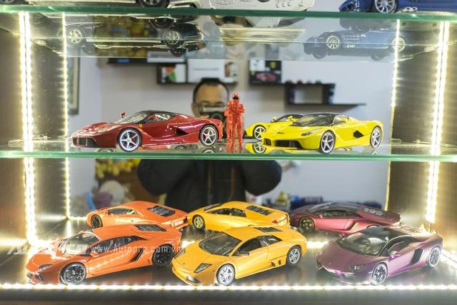 Tay đua mô hình bên những chiếc siêu xe như Ferrari và Lamborghini.
