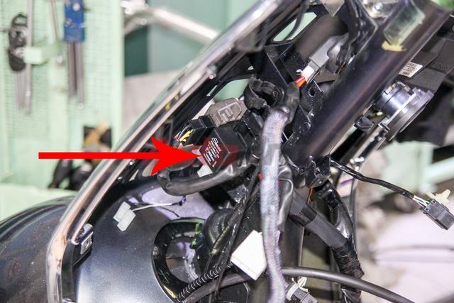 Rơ-le nháy xi-nhan nằm phía dưới sạc. Để tiếp cận các chi tiết ở phần yếm, bắt buộc kỹ thuật viên phải tháo mảng yếm liền với phần để chân phía dưới.