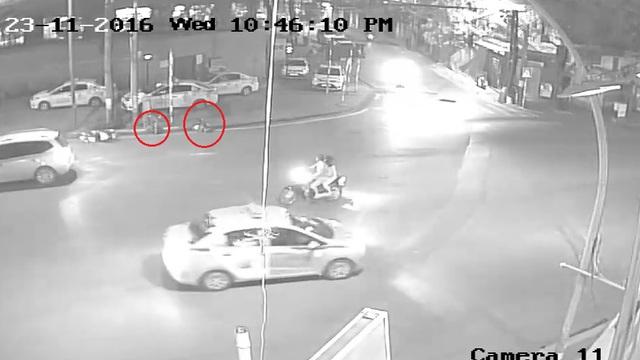 Hai người đi xe máy bị hất văng vào lề đường sau va chạm. Ảnh cắt từ video
