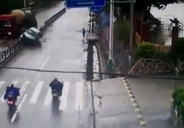 Ô tô con leo lên dải phân cách sau khi tạt đầu xe tải. Ảnh cắt từ video