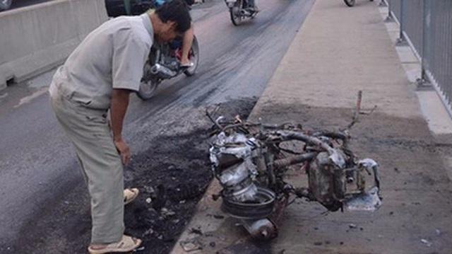 Người đàn ông thẫn thờ bên chiếc xe bốc cháy trơ khung ở Sài Gòn