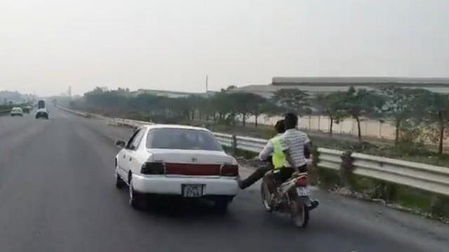 Bàn chân vàng trong làng cứu hộ: Nam thanh niên đi xe máy dùng chân không đẩy ô tô chạy băng băng trên cao tốc