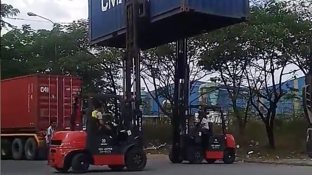 Clip: 2 tài xế xe nâng phối hợp như diễn xiếc để chuyển chiếc thùng container từ xe này sang xe khác
