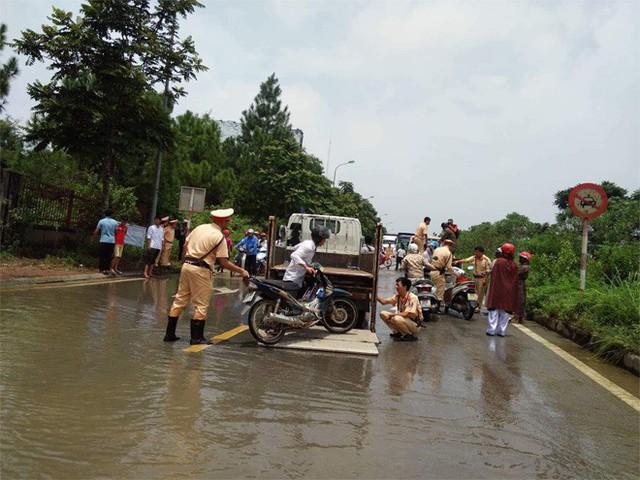 CSGT Hà Nội dùng xe chuyên dụng đưa dân qua vùng ngập - Ảnh 3.