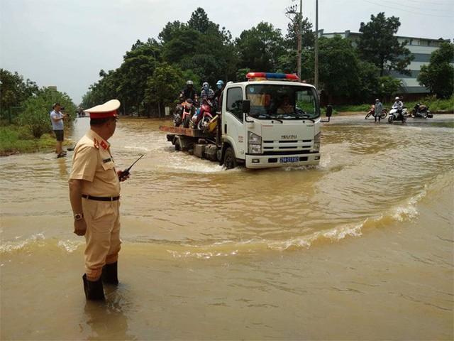 CSGT Hà Nội dùng xe chuyên dụng đưa dân qua vùng ngập - Ảnh 9.