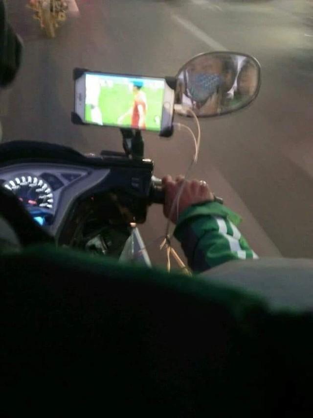 Vừa lái xe vừa dùng điện thoại xem Việt Nam đá, tài xế xe ôm khiến nhiều người lo lắng - Ảnh 1.