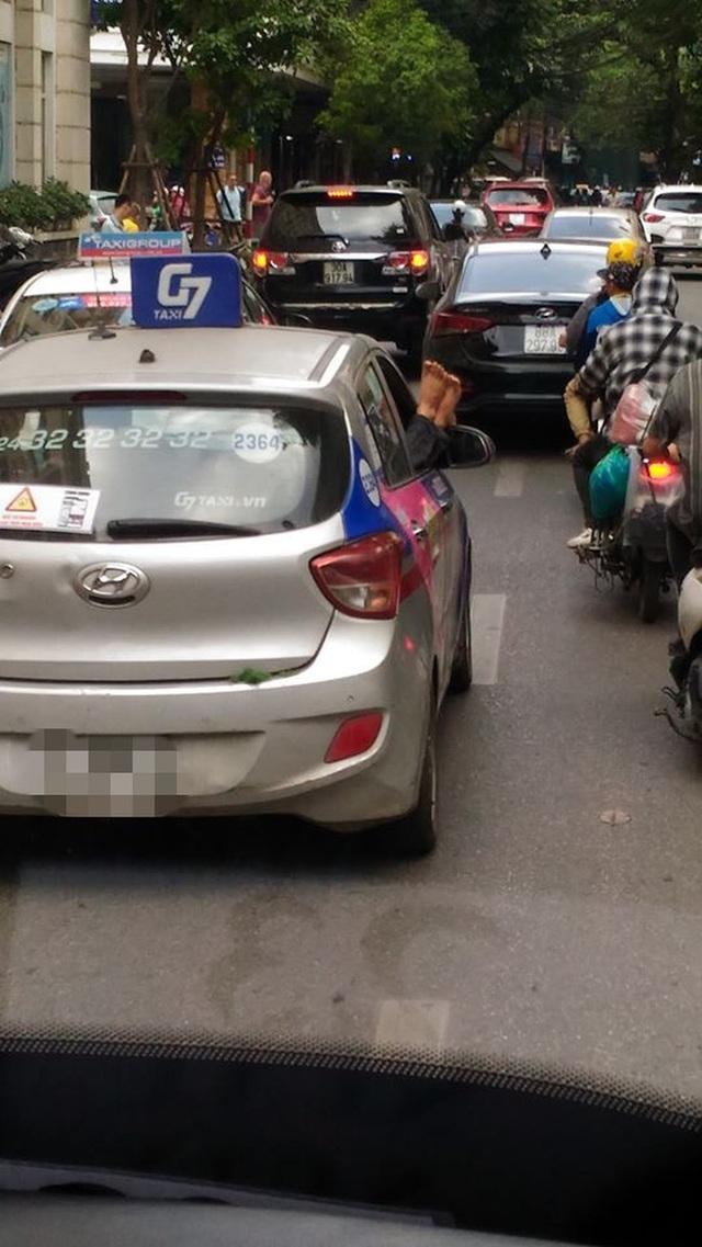 Hình ảnh thượng đế thò đôi chân kém duyên từ cửa xe taxi ở Hà Nội - Ảnh 1.