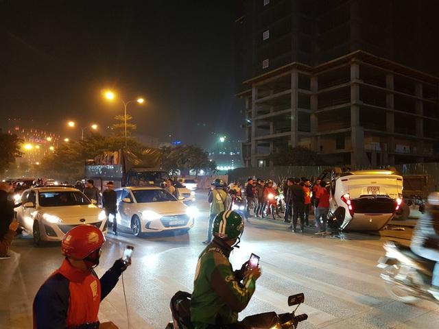 Giữa dòng người đi bão mừng U22 Việt Nam giành HCV, ô tô trắng lật giữa phố Hà Nội - Ảnh 1.