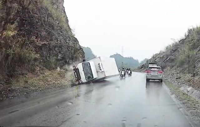 Clip: Xe tải ôm cua mất lái đâm vào sườn núi rồi lật ngang, hàng loạt xe máy may mắn thoát tai nạn trong gang tấc - Ảnh 2.