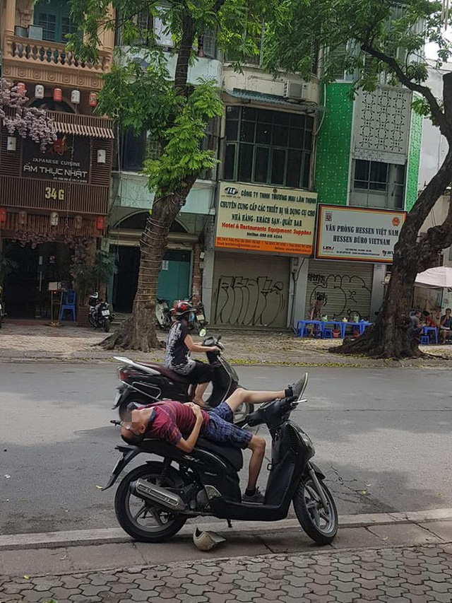 Người đàn ông nằm trên xe SH với tư thế kỳ lạ giữa đường khiến nhiều người chú ý - Ảnh 1.