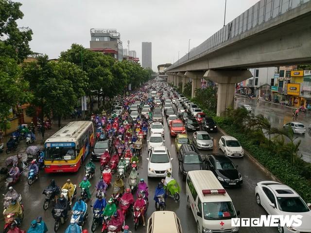 Ảnh: Xe cộ ùn tắc khắp ngả, người dân vất vả mưu sinh dưới trời mưa bão ở Thủ đô - Ảnh 1.