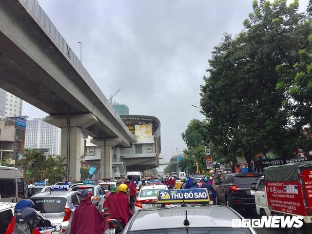 Ảnh: Xe cộ ùn tắc khắp ngả, người dân vất vả mưu sinh dưới trời mưa bão ở Thủ đô - Ảnh 2.