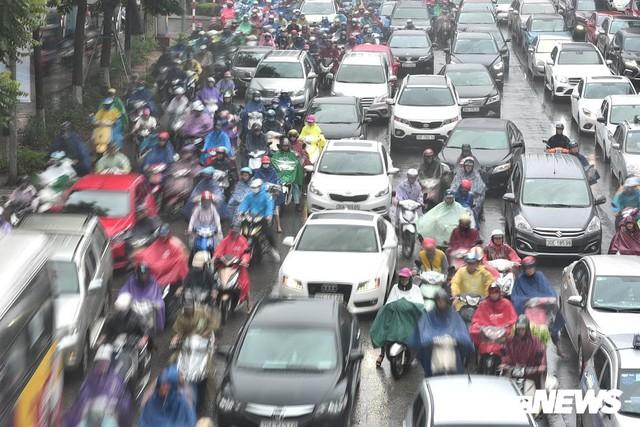 Ảnh: Xe cộ ùn tắc khắp ngả, người dân vất vả mưu sinh dưới trời mưa bão ở Thủ đô - Ảnh 3.