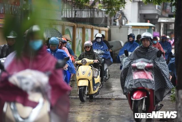 Ảnh: Xe cộ ùn tắc khắp ngả, người dân vất vả mưu sinh dưới trời mưa bão ở Thủ đô - Ảnh 5.