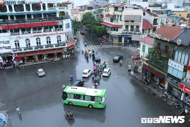Ảnh: Xe cộ ùn tắc khắp ngả, người dân vất vả mưu sinh dưới trời mưa bão ở Thủ đô - Ảnh 6.