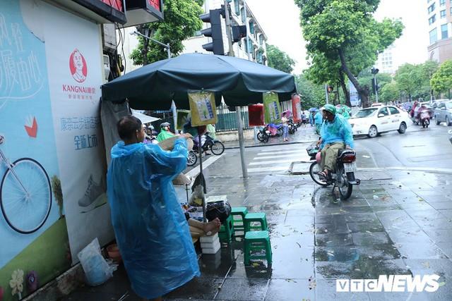 Ảnh: Xe cộ ùn tắc khắp ngả, người dân vất vả mưu sinh dưới trời mưa bão ở Thủ đô - Ảnh 7.