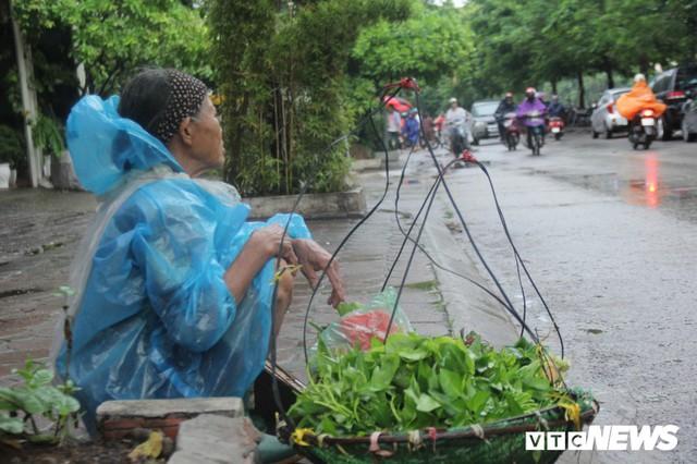 Ảnh: Xe cộ ùn tắc khắp ngả, người dân vất vả mưu sinh dưới trời mưa bão ở Thủ đô - Ảnh 8.