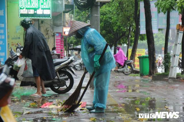Ảnh: Xe cộ ùn tắc khắp ngả, người dân vất vả mưu sinh dưới trời mưa bão ở Thủ đô - Ảnh 10.