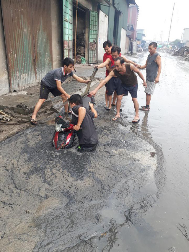 Tình huống éo le: Chiếc xe máy bị đường lớn nuốt đầu trong ngày mưa lớn - Ảnh 1.