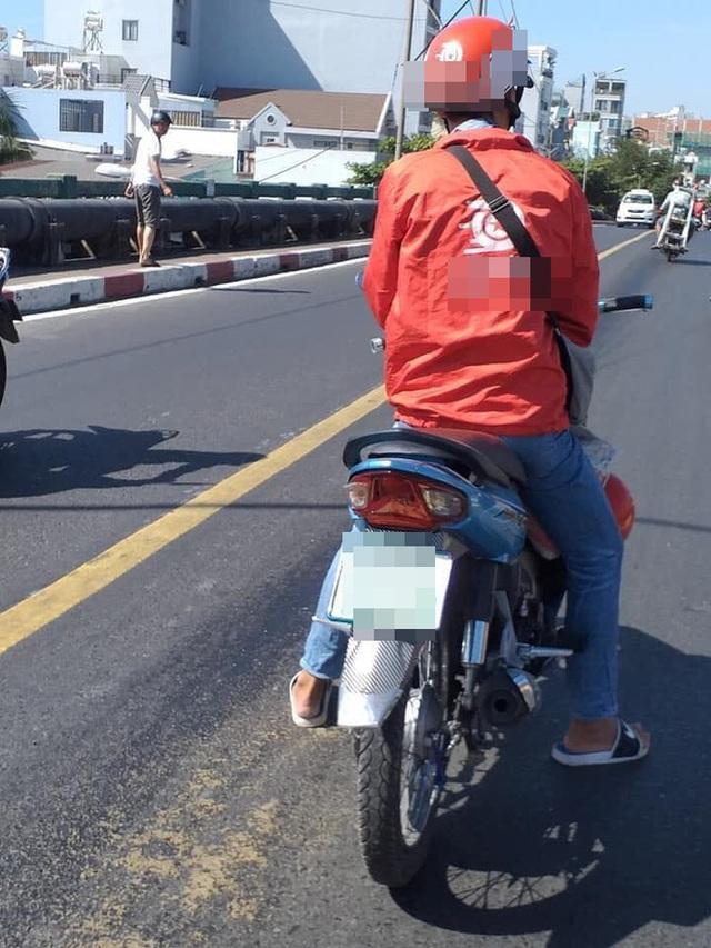 Thấy vết dầu nhớt tràn trên đường, thanh niên chạy xe ôm có hành động đẹp ngay ngày đầu năm mới - Ảnh 2.
