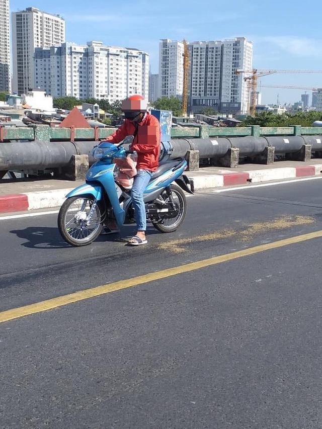 Thấy vết dầu nhớt tràn trên đường, thanh niên chạy xe ôm có hành động đẹp ngay ngày đầu năm mới - Ảnh 1.