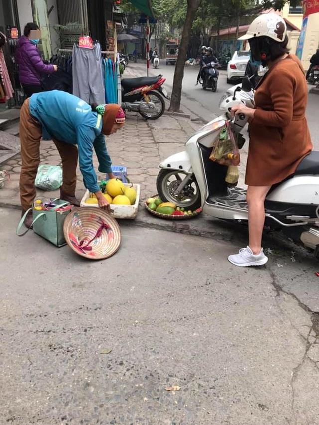 Bức xúc người phụ nữ cán nát mẹt hoa quả của cô bán hàng rong vì ngồi chắn cửa - Ảnh 2.