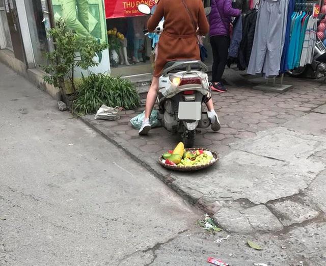 Bức xúc người phụ nữ cán nát mẹt hoa quả của cô bán hàng rong vì ngồi chắn cửa - Ảnh 3.