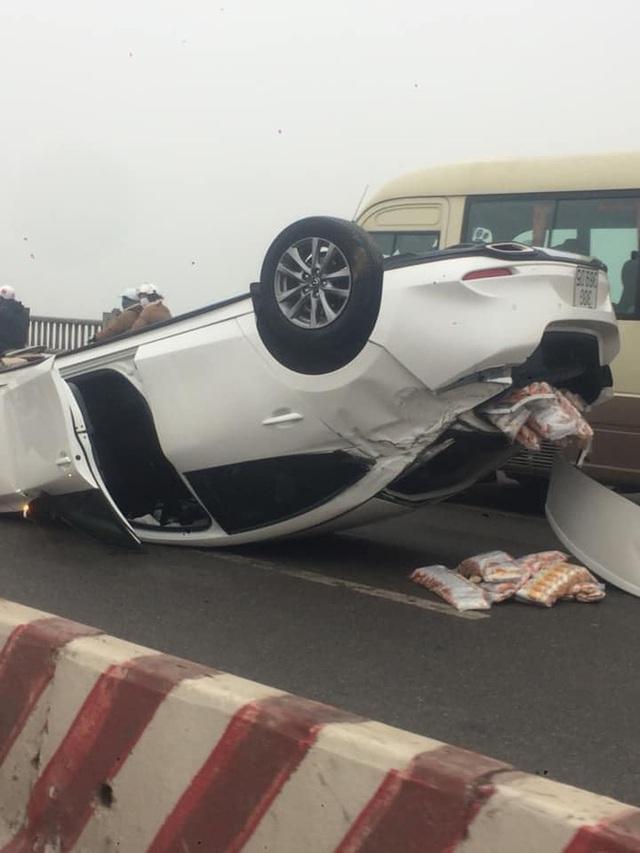 Hà Nội: Xe Mazda đâm vào dải phân cách, lật ngửa trên cầu Vĩnh Tuy gây ùn tắc nghiêm trọng - Ảnh 1.