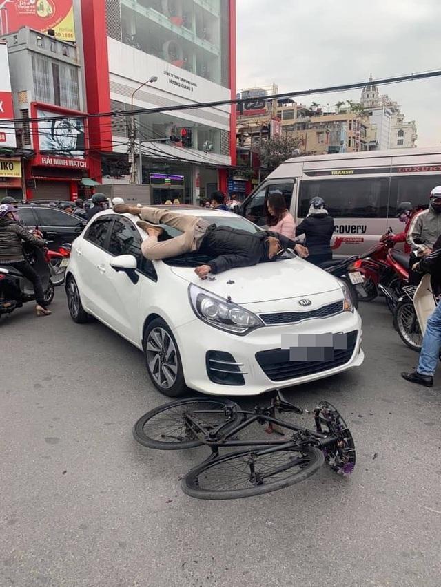 Va chạm giao thông không hòa giải được, chủ xe đạp leo lên nắp capo ô tô nằm - Ảnh 1.