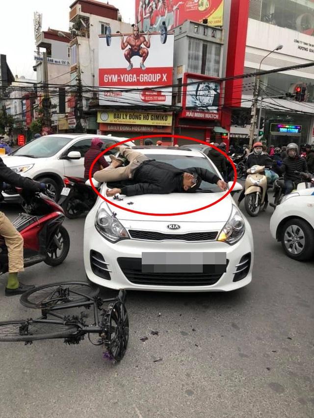 Va chạm giao thông không hòa giải được, chủ xe đạp leo lên nắp capo ô tô nằm - Ảnh 2.