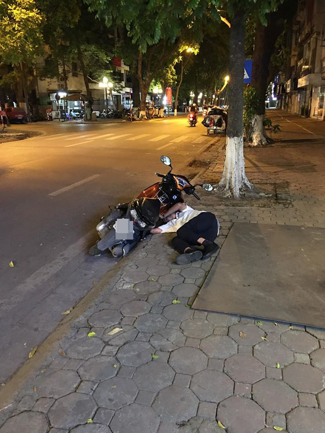 Đang đi đường, thanh niên áo trắng bỗng bỏ xe máy rồi lên vỉa hè nằm... ngủ - Ảnh 1.