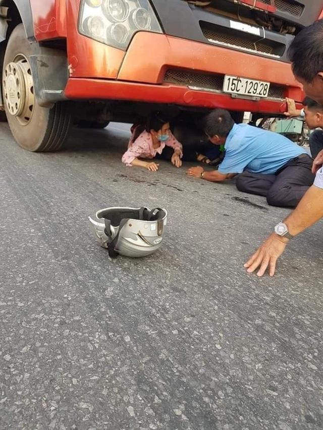 CLIP: Bị xe máy kẹp chặt chân dưới gầm xe container, người phụ nữ khiến đám đông hoảng hốt giải cứu - Ảnh 2.