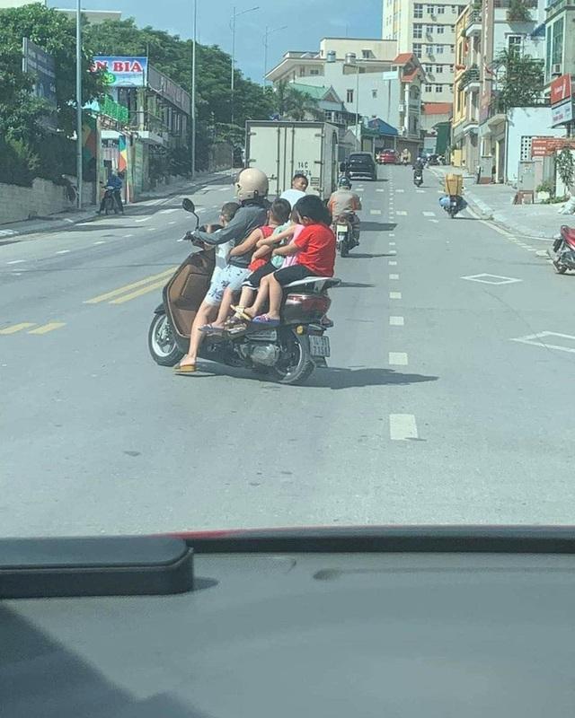 Thót tim hình ảnh người phụ nữ liều lĩnh để 5 em nhỏ không đội mũ bảo hiểm ngồi vắt vẻo, chật ních chiếc xe gắn máy - Ảnh 1.