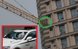 Cần cẩu đập vào tòa cao ốc ở Sài Gòn, đá rơi đè nát đầu xe sang