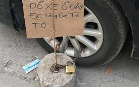 """Hà Nội: Đỗ xe trên vỉa hè rồi bỏ đi mất, tài xế Camry được """"tặng"""" thêm cục bê tông vào bánh trước"""