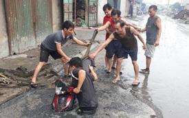 """Tình huống éo le: Chiếc xe máy bị đường lớn """"nuốt"""" đầu trong ngày mưa lớn"""