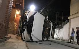 Xế hộp đâm gãy cột điện rồi lật nghiêng giữa đường, người trong xe bò ra từ cửa sổ trời