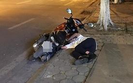 Đang đi đường, thanh niên áo trắng bỗng bỏ xe máy rồi lên vỉa hè nằm... ngủ